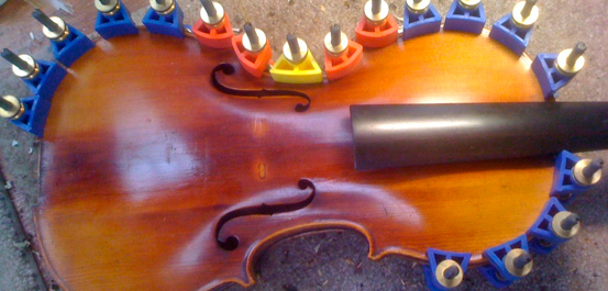 After repairing cracks in the top of the violin, and the glue has set, we're in the process of removing clamp.